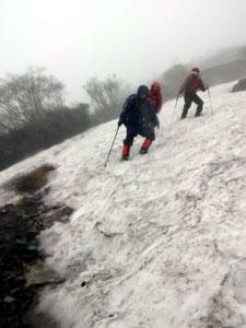 残雪で覆われた登山道。急傾斜の雪上をアイゼンやピッケルを使って慎重に足を進める登山者