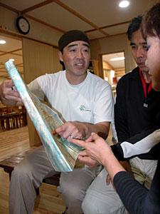 地図を開き、登山者にアドバイスする高妻潤一郎さん(左)