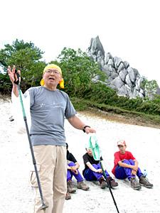 鳳凰三山・地蔵ケ岳山頂のオベリスクの前で南アルプスの歴史や魅力を伝える清水准一さん