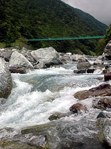 川のせせらぎが人々を迎える広河原。野呂川に架かるつり橋を渡って多くの登山者が高峰へ向かう