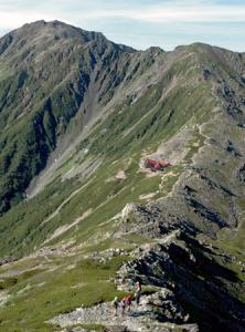 絶 景 北岳から間ノ岳(写真左奥)までの稜線を望む。手前の登山者の行く手には北岳山荘(写真中央)が見える