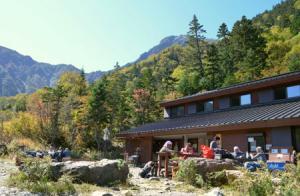 登山者でにぎわう白根御池小屋。小屋の周辺では、ナナカマドやダケカンバの木々の葉が赤や黄色に色づいている