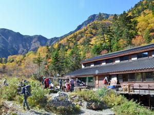 登山客でにぎわう白根御池小屋。周囲の木々は色づき、多くの登山客が写真を撮るなどして紅葉を楽しんでいた