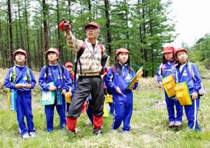 地元の小学生を案内し、景観の特徴を教える甘利山倶楽部の市川秀明さん=韮崎・甘利山