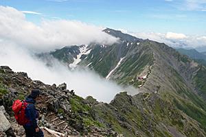 天候が回復して晴れ間が広がり、北岳から間ノ岳(中央)に続く稜線(りょうせん)を望む。鞍部(あんぶ)には北岳山荘が確認できる