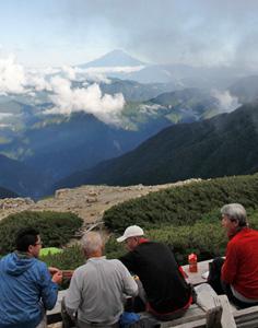 <眺望> 富士山を眺めながら食事をとる登山者。国内最高峰を望む絶景は、疲れ切った体を癒やしてくれる