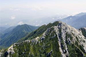 ピラミッドのような山容の甲斐駒ケ岳。左奥から山頂にかけて開山ルートとなった黒戸尾根が延びる=山日YBSヘリ「ニュースカイ」(NEWSKY)から