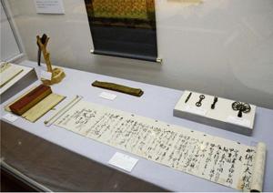 小尾権三郎の父から山田家に贈られた遺品。祈誓文が書かれた巻物(手前)や祈祷に用いる金銅製の法具(右奥の左側3点)などがある=北杜市郷土資料館