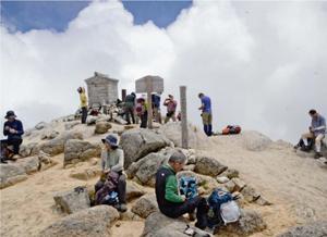 登山者でにぎわう頂上。複数のルートやアクセス道路が開かれ、多くの人が眺望を楽しめるようになった=甲斐駒ケ岳山頂