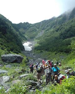 登山者:北岳を目指して大樺沢の登山道を登る登山者。奥には雪渓が見える(写真左)