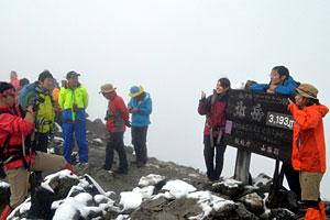 7日に初冠雪を観測した北岳山頂。霧の中を登頂し、記念撮影をする登山者も目立った