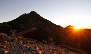 <照らされる峰> 昇る朝日に照らし出される北岳。太陽が徐々に姿を現すと、周辺はオレンジ色に染まり、登山者から歓声が上がった