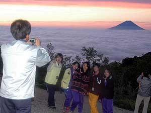 富士山の朝焼けをバックに記念撮影する人々