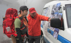 写真で山頂付近の雪の様子を確認する登山客(左)=南アルプス市芦安芦倉