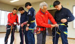 竹内敬一隊長(右から2番目)からロープワークの指導を受ける署員=北杜署