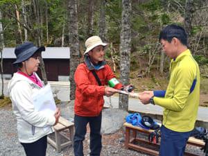 長野県側から訪れた登山者(右)に啓発チラシを手渡す芦安ファンクラブのメンバー=南アルプス・北沢峠