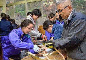 輪かんじき作りに取り組む生徒と芦安ファンクラブのメンバー=芦安中