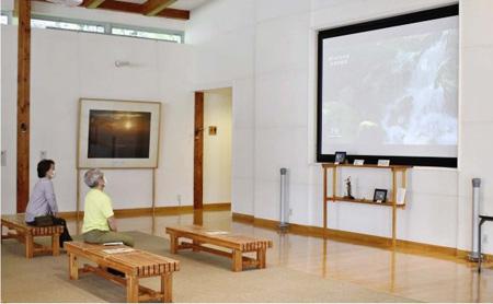 北岳を紹介する映像などを映す無料コーナーの大型スクリーン=南アルプス市芦安山岳館